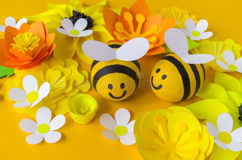 Miel del d?a de fiesta Fondo amarillo Huevo pintado abeja de la artesan?a Semana Santa Flor de papel de la papiroflexia deletread foto de archivo libre de regalías
