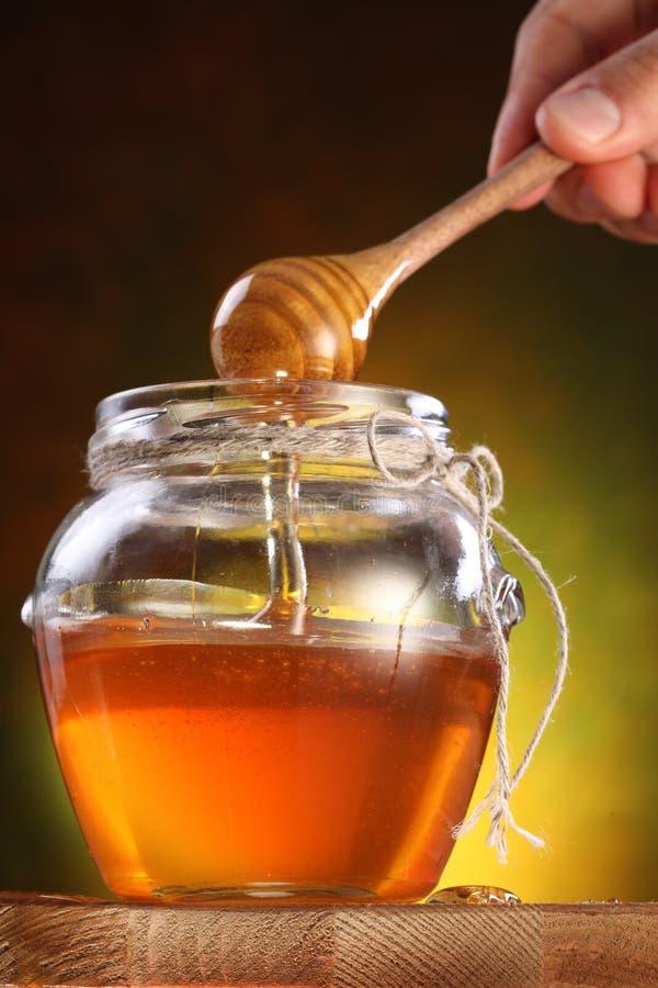 Miel dulce que vierte de drizzler en el crisol. foto de archivo libre de regalías