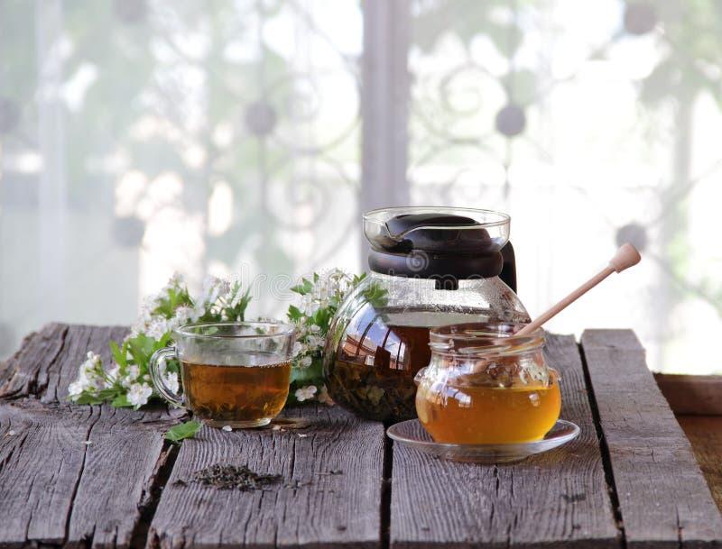 Miel en el banco transparente y té en una taza transparente fotos de archivo libres de regalías