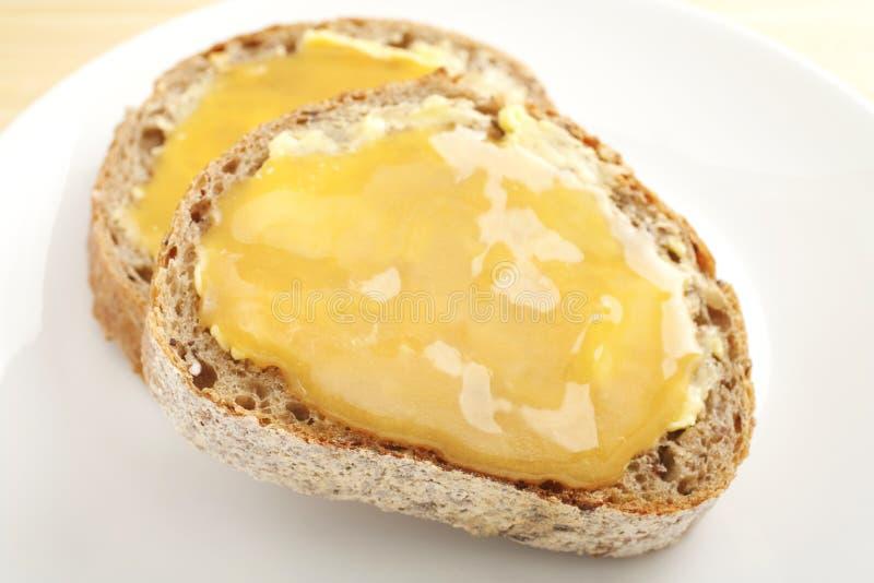 Miel en el pan integral fotografía de archivo libre de regalías