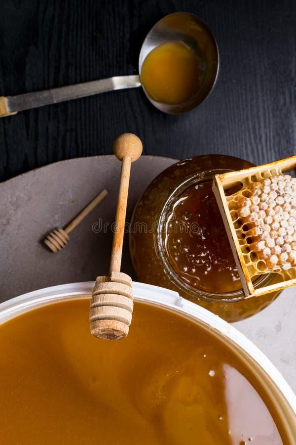 Miel en el tarro y cubo grande, panal y palillo de madera, cucharón del metal fotos de archivo