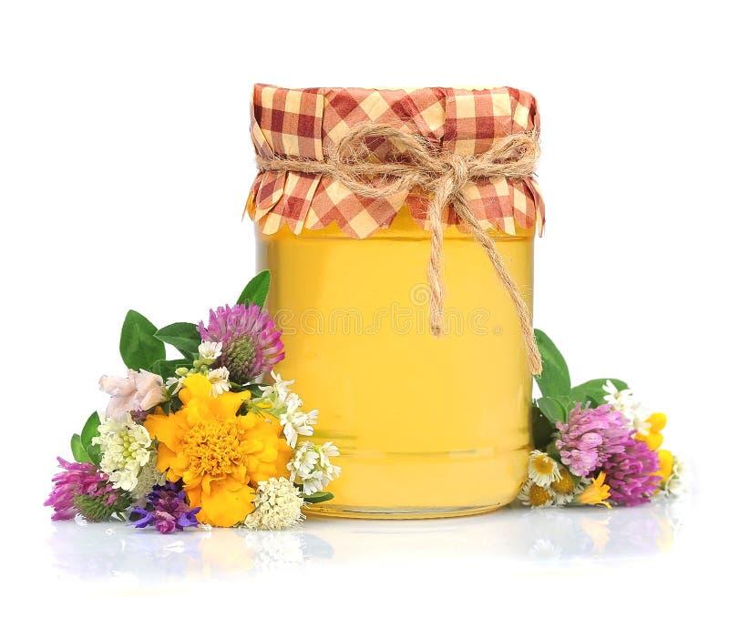 Miel en los tarros de cristal con las flores foto de archivo