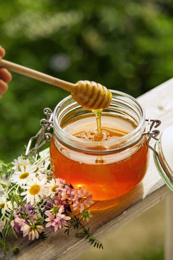 Miel en pot de verre avec des abeilles volantes et fleurs sur un plancher en bois image stock