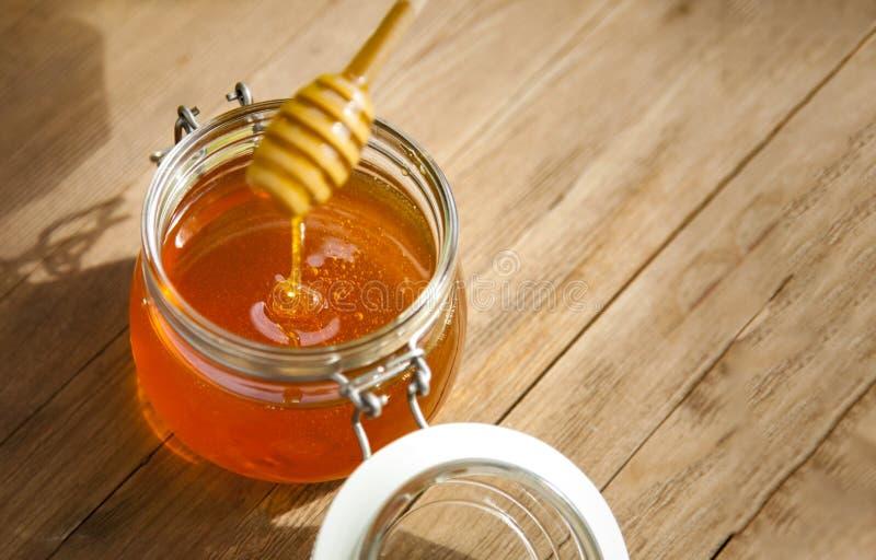 Miel en pot de verre sur parquet photo stock