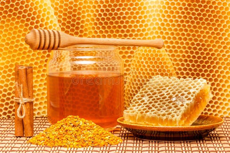 Miel en tarro con el cazo, el panal, el polen y el ci foto de archivo libre de regalías