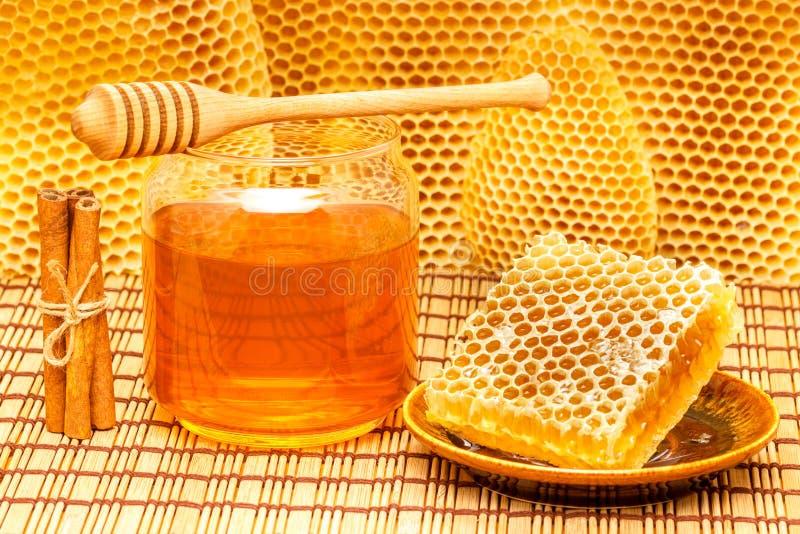 Miel en tarro con el cazo, el panal y el canela o fotografía de archivo