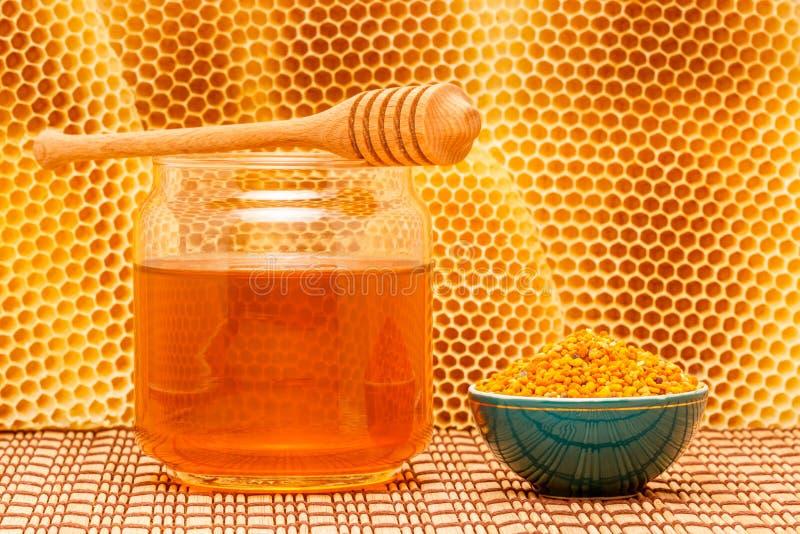 Miel en tarro con el cazo, el panal y el polen adentro foto de archivo