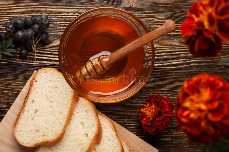 Miel en un bol de vidrio con las rebanadas de pan blanco foto de archivo