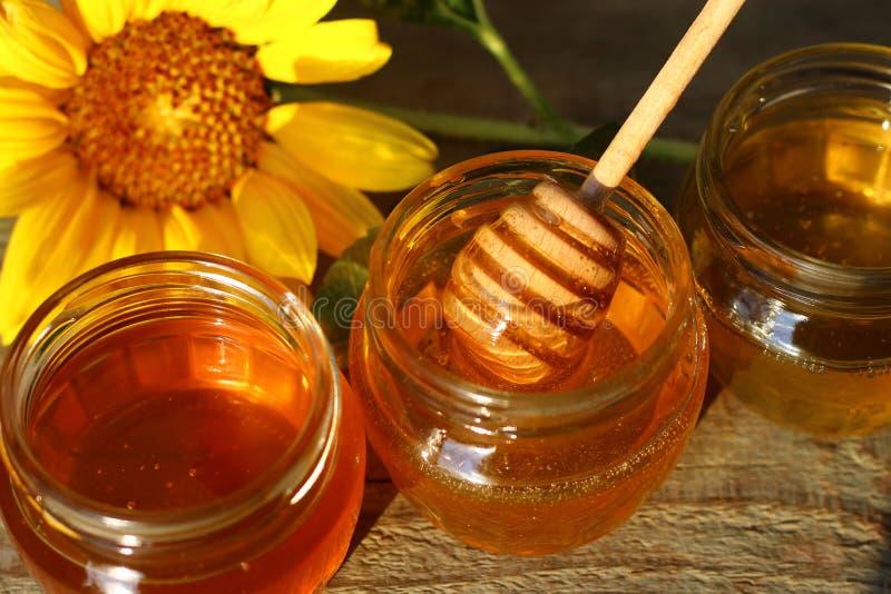 Miel en un tarro de cristal con las flores en el piso de madera fotos de archivo