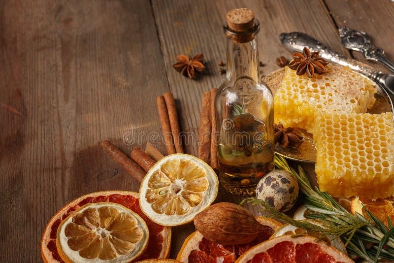 Miel, especias y frutas secadas en una tabla rústica Ingredientes imagen de archivo