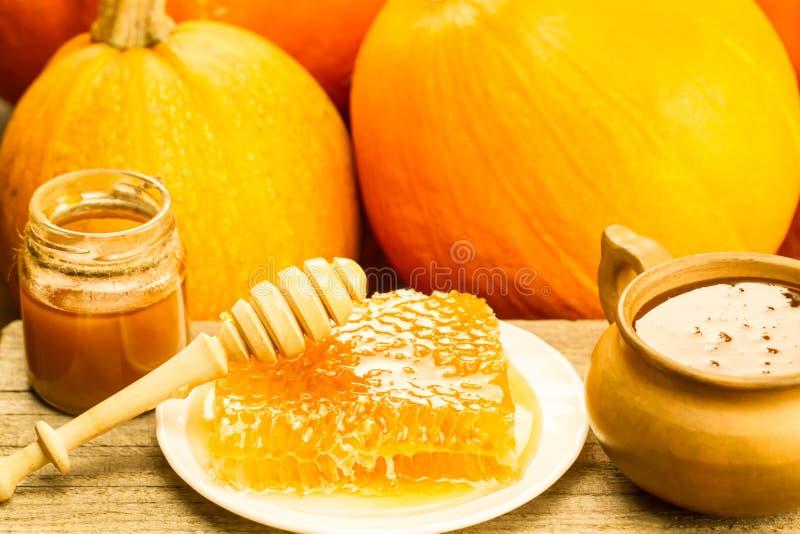 Miel et drizzler frais sur un fond en bois Style d'automne, nid d'abeilles, potiron images stock