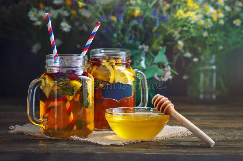 Miel, fleurs de champ, thé de citron et fruit frais sur une table en bois Foyer sélectif image libre de droits