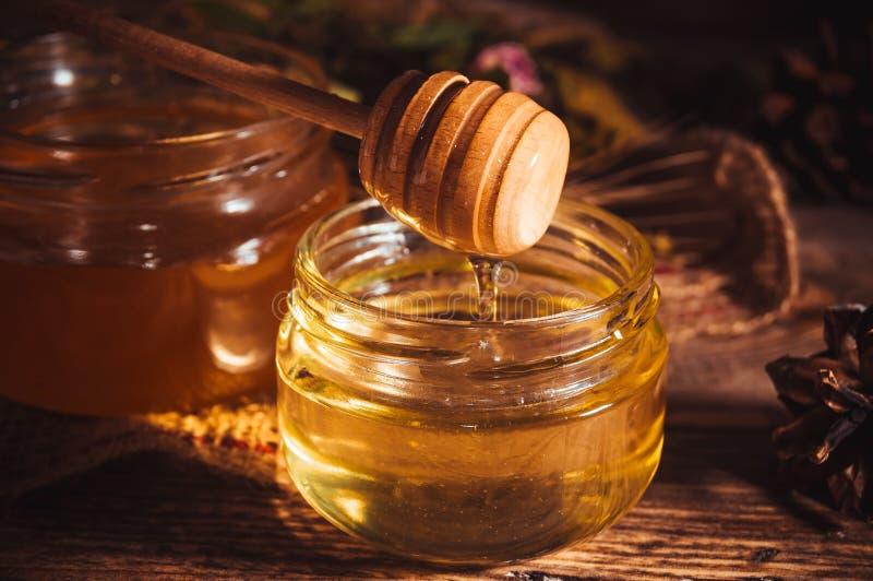 Miel frais d'été dans le pot en verre et le plongeur en bois de miel sur le fond rustique images libres de droits