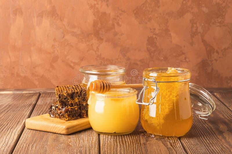 Miel frais d'or dans divers pots et nids d'abeilles en verre sur la table en bois Collage des légumes frais Fond brun rustique photo libre de droits
