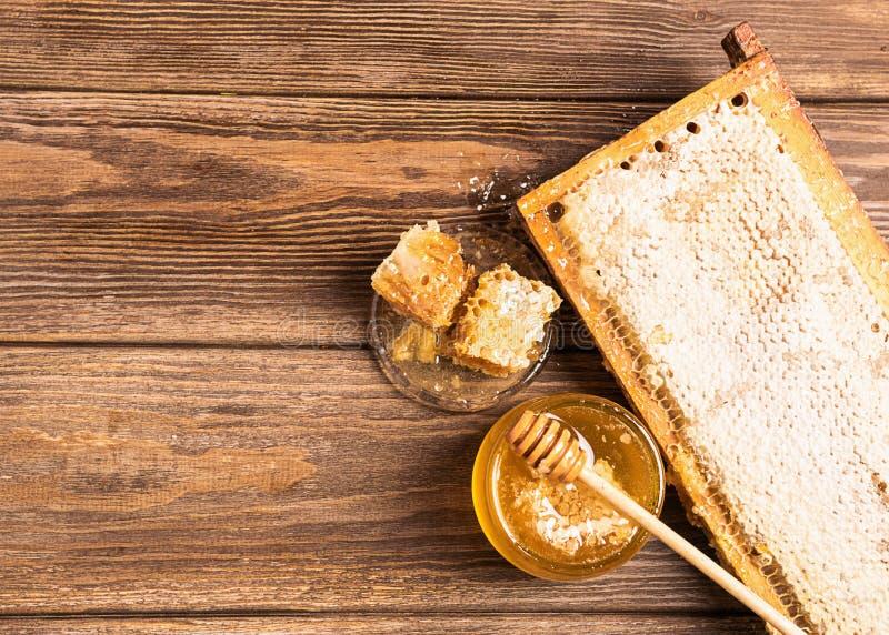 Miel fresca de oro con los tarros y panales y cuchara de la miel en fondo de madera marrón El concepto de productos naturales imagenes de archivo