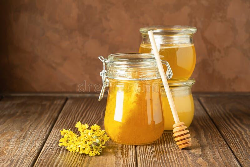 Miel fresca de oro en fondo rústico marrón de los diversos tarros de cristal El concepto de productos naturales Marco horizontal foto de archivo libre de regalías