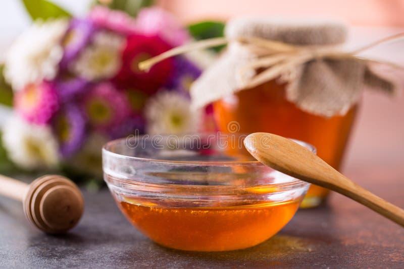 Miel normal Miel au pot en verre et à l'arrière-plan en bois de plongeur photographie stock