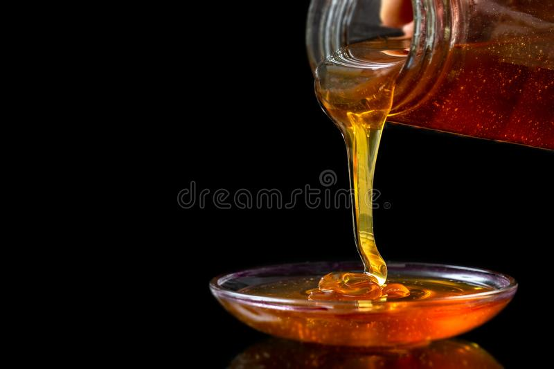 Miel organique liquide d'or versant du pot sur le bacgrond noir images stock