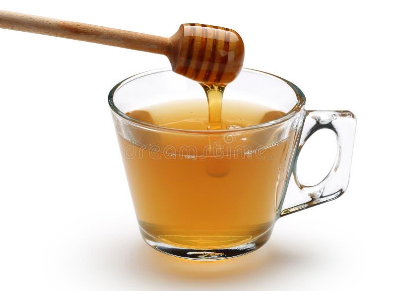 Miel que vierte de cazo de madera en una taza imagen de archivo