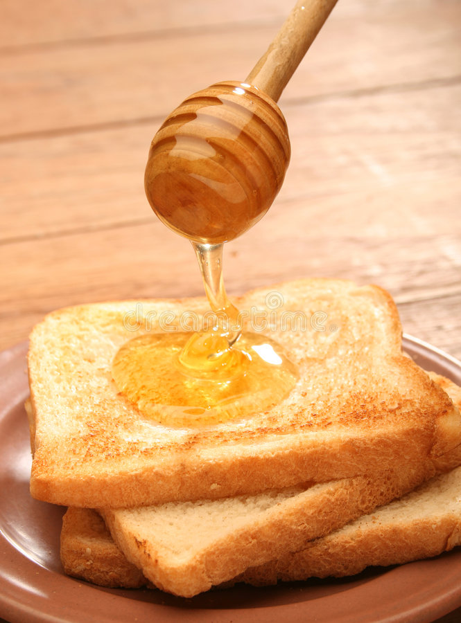 Miel que vierte sobre el pan de la tostada foto de archivo libre de regalías