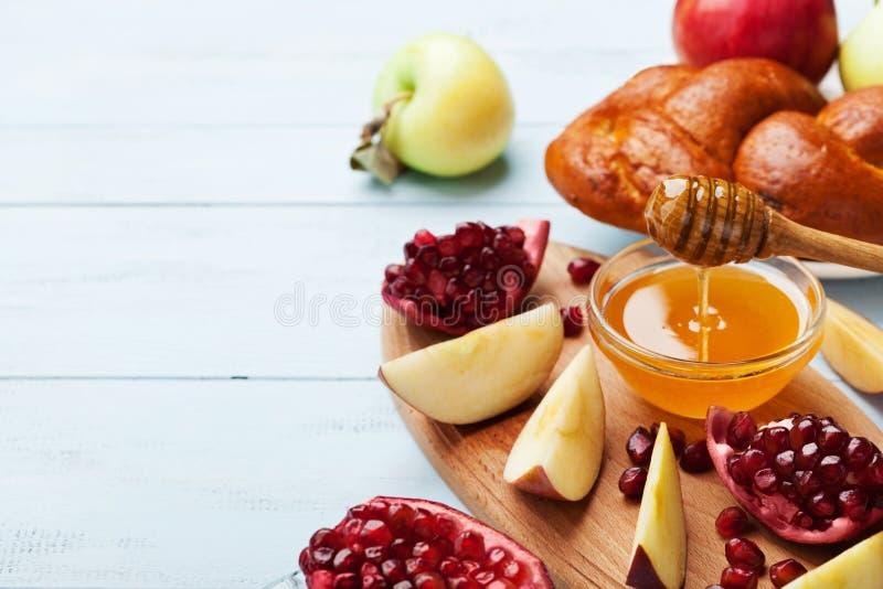 Miel, rebanadas de la manzana, granada y hala La tabla fijó con la comida tradicional para el día de fiesta judío del Año Nuevo,  imagen de archivo