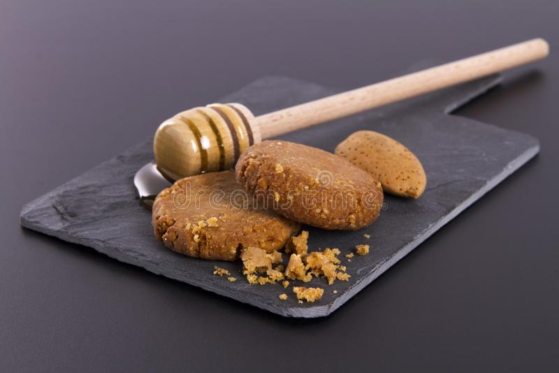Miel y galletas en una pizarra de la cartulina en un fondo negro imagen de archivo libre de regalías