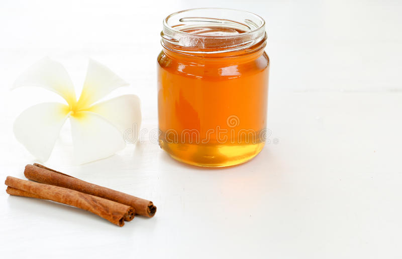 Miele, cannella con la plumeria su fondo bianco immagini stock