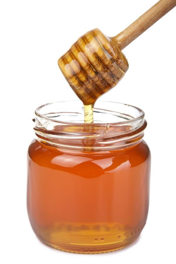 Miele che versa in vaso isolato immagine stock libera da diritti