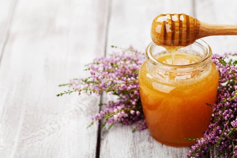Miele di versamento in barattolo e nell'erica dei fiori sulla tavola rustica di legno Copi lo spazio per testo fotografia stock