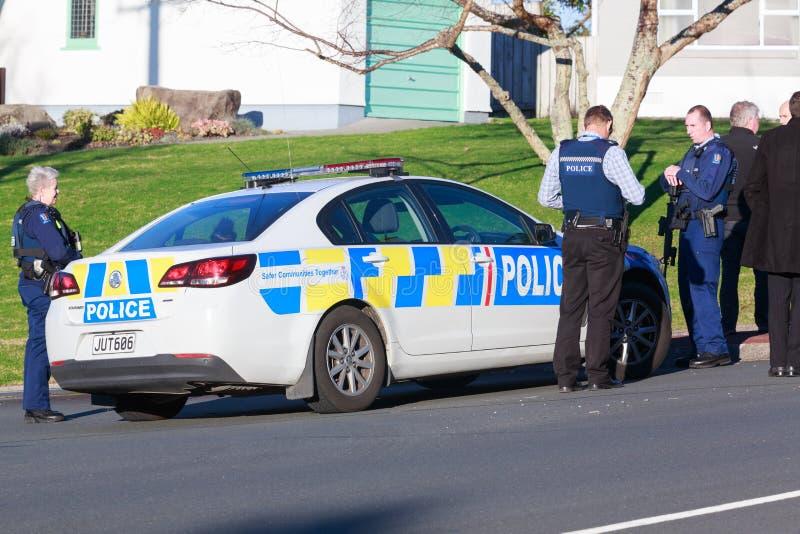 Miembros armados de la fuerza de policía de Nueva Zelanda alrededor del coche policía foto de archivo libre de regalías