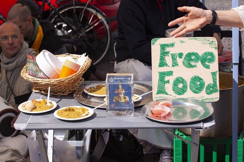 Miembros de Krishna de las liebres con la muestra que ofrece la comida libre en la calle foto de archivo libre de regalías