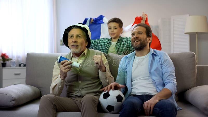 Miembros de la familia masculinos que apoyan el fútbol francés, campeonato de observación en casa fotografía de archivo libre de regalías