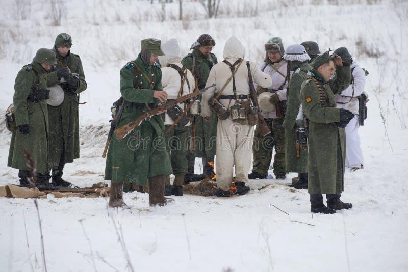 Miembros de la reconstrucción militar-histórica bajo la forma de soldados de Wehrmacht antes de la batalla Un fragmento del festi imagen de archivo libre de regalías