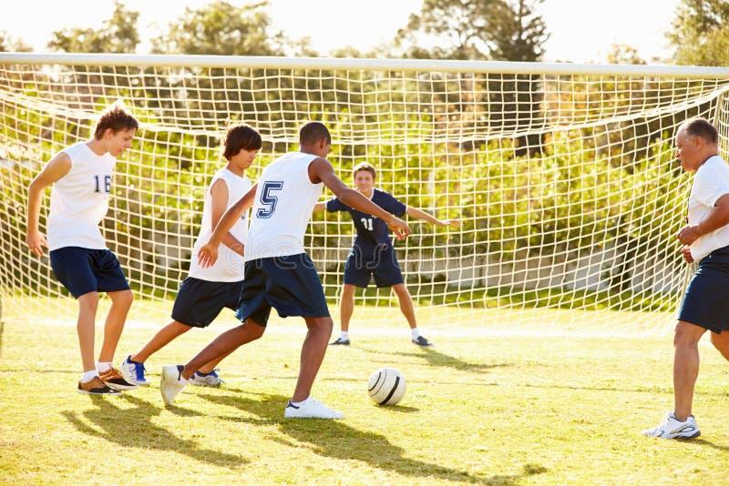 Miembros del fútbol masculino de la High School secundaria que juega el partido imagen de archivo libre de regalías