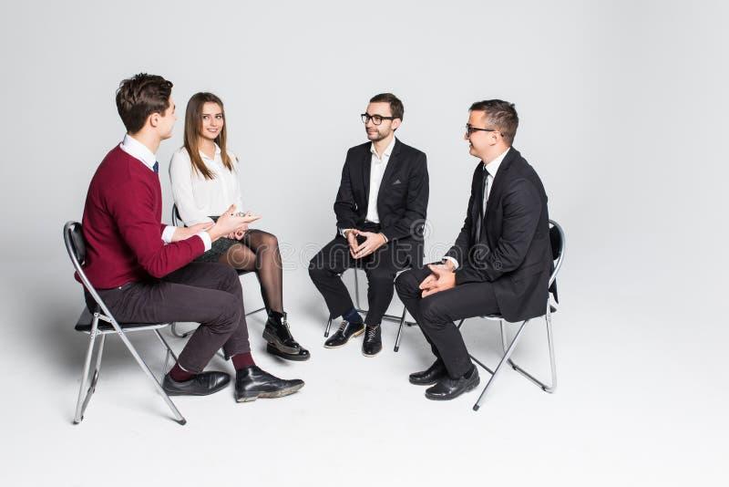 Miembros del grupo de ayuda que se sientan en las sillas que tienen reunión aislados en el fondo blanco fotografía de archivo libre de regalías