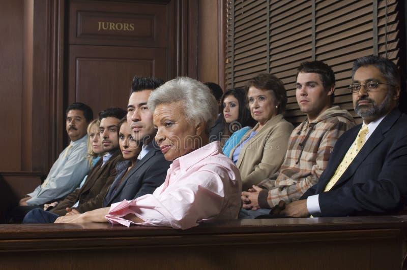Miembros del jurado que se sientan en sala de tribunal fotos de archivo