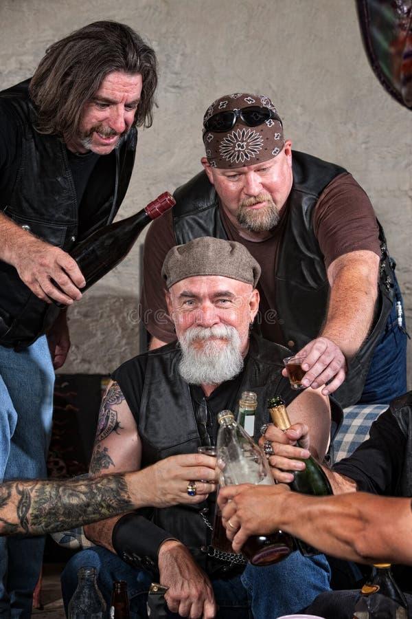 Miembros felices de la cuadrilla con alcohol imagen de archivo