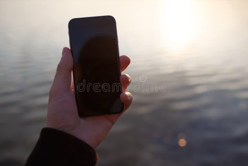 Mienia smartphone wewnątrz oddaje zmierzchu tło zdjęcie stock