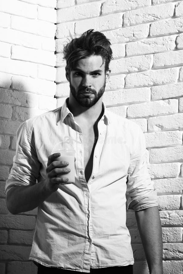 Mienia szkło nonalcoholic koktajl na ściana z cegieł tle, przystojny brodaty macho seksowny mężczyzna obrazy stock