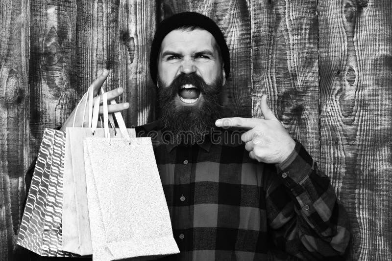 Mienie zakupy pakunki w czerwonej czarnej w kratkę koszula na brown drewnianym rocznika studia tle Brodaty brutalny obraz stock