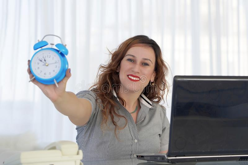 mienie zegarowa kobieta Miedzianow?osa kobieta trzyma budzika w jej r?ce w miejsce pracy obrazy stock
