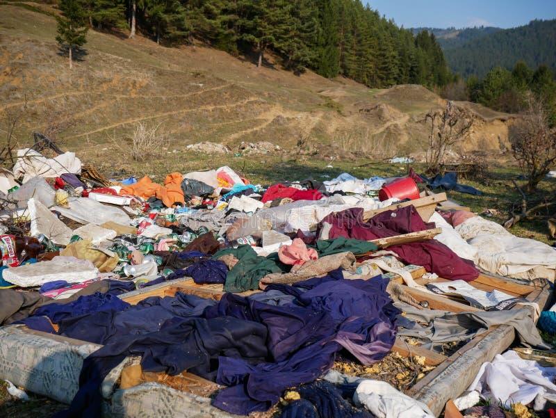 Human trash near pine forest, conceptual image of human negligence. Miercurea Ciuc, Romania-01 April 2019: Human trash near pine forest, conceptual image of stock image