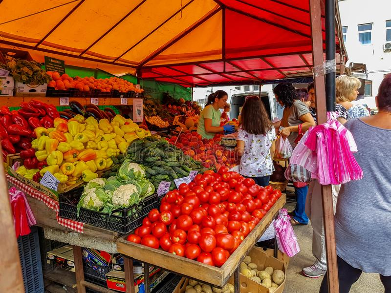 People buying fresh fruits and vegetables at the local market. stock image