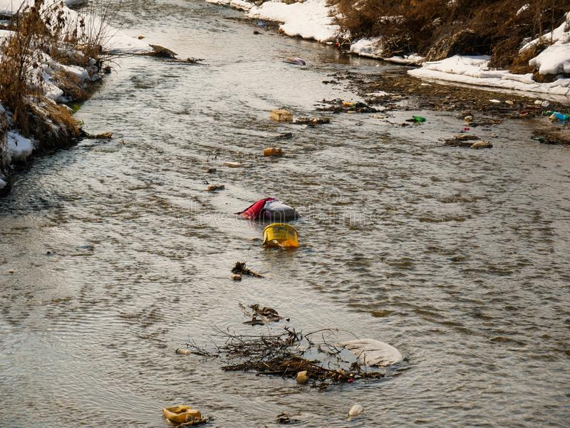 Human trash in the clean small river, conceptual image of negligence. Miercurea Ciuc, Romania-02 March 2019: Human trash in the clean small river, conceptual royalty free stock images