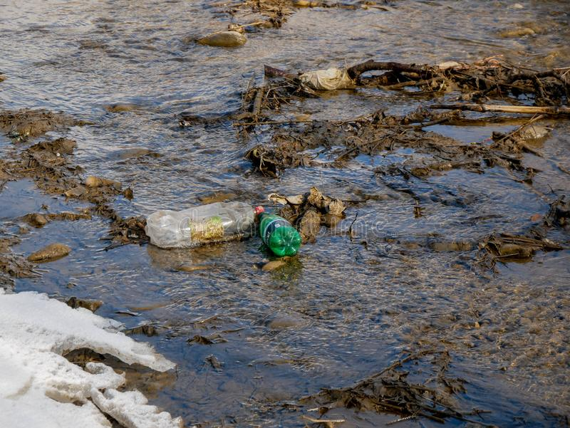 Human trash in the clean small river, conceptual image of negligence. Miercurea Ciuc, Romania-02 March 2019: Human trash in the clean small river, conceptual stock photos
