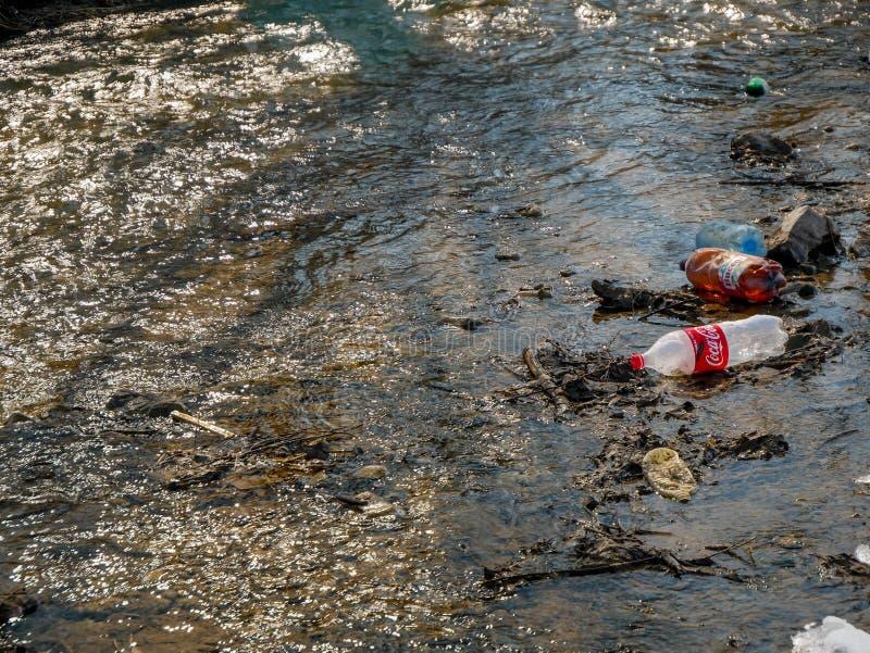 Human trash in the clean small river, conceptual image of negligence. Miercurea Ciuc, Romania-02 March 2019: Human trash in the clean small river, conceptual royalty free stock image