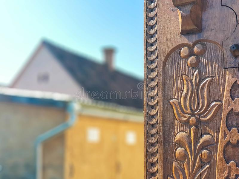 Detailed hand carved tulip on traditional hungarian oak wood gate pylon . royalty free stock photos