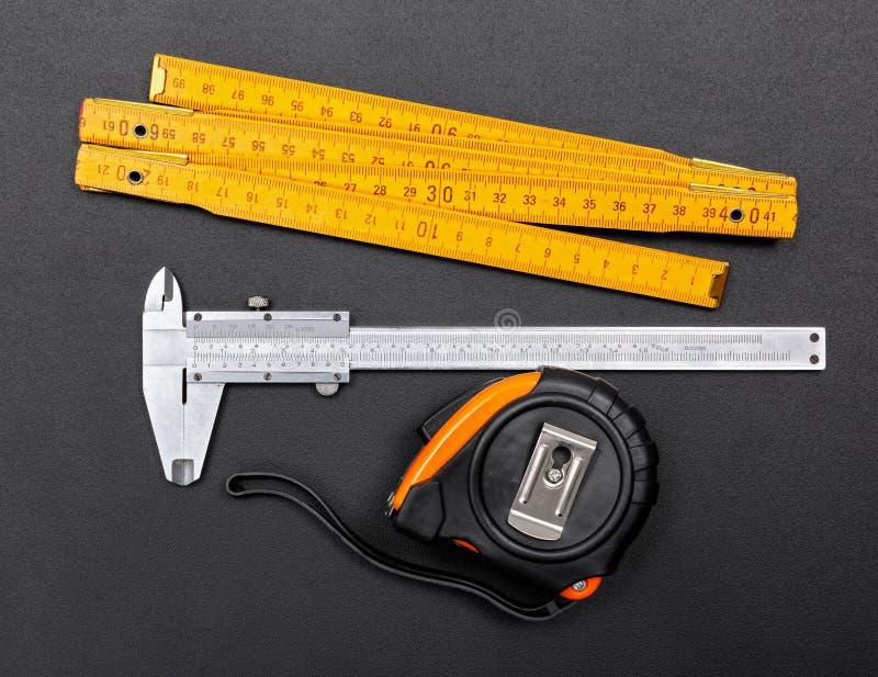 Mierzyć narzędzia na czerni: władca, caliper i taśma, zdjęcia stock
