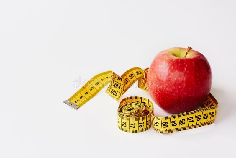 Mierzy taśmy i świeżej owoc jabłka na białym tle Strata ciężar, szczupły ciało, zdrowej diety pojęcie obrazy stock