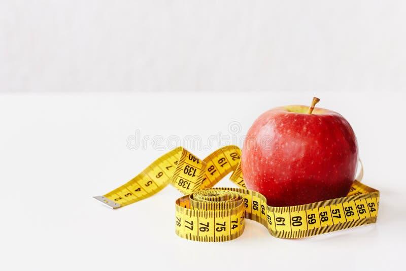 Mierzy taśmy i świeżej owoc jabłka na białym tle Strata ciężar, szczupły ciało, zdrowej diety pojęcie fotografia royalty free